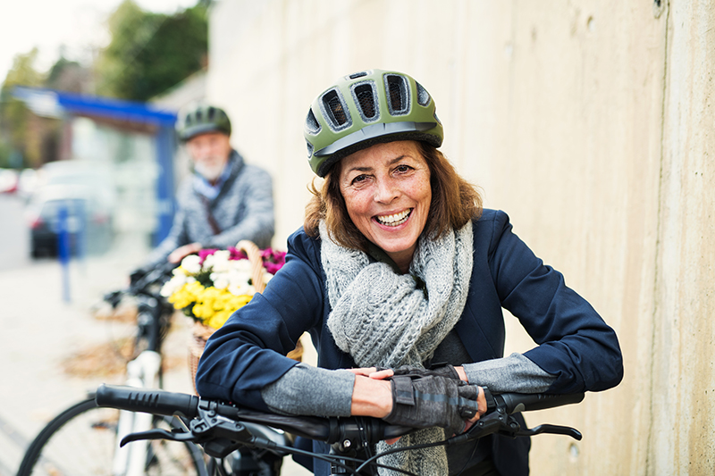 Frau am Fahrrad mit Helm