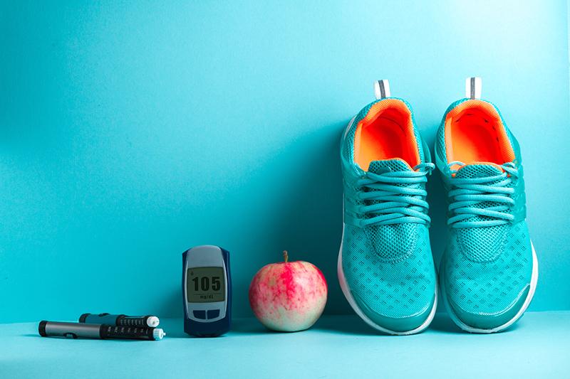 Sportschuhe mit Apfel und Messgerät