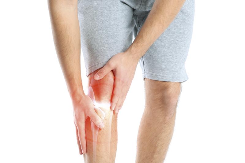 Mann fasst sich ans Bein