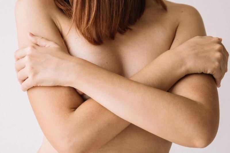 Nackte Frauenbrust mit Armen verdeckt